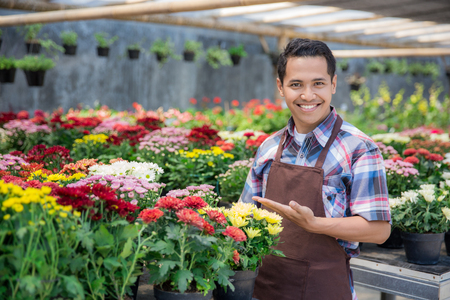 Happy asian male florist working flower gardening shop Stock Photo