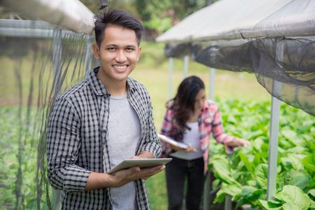 현대 hydrophonic 농장에서 태블릿으로 행복 한 남자의 초상화