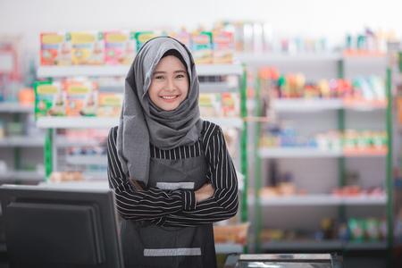 スーパーマーケットの現金カウンターに立っている笑顔のムスリムアジア人女性スタッフのポートレート