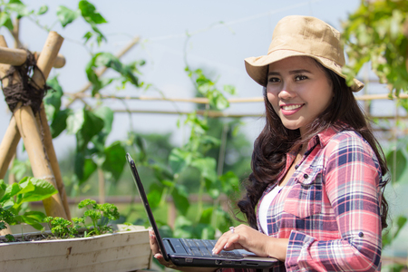 woman using laptop whie working in the farm. modern farming concept Banco de Imagens