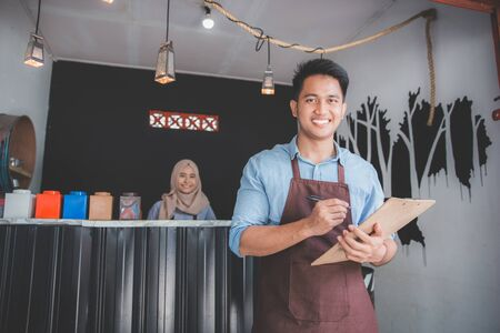 Happy asian male waiter in apron writing order Zdjęcie Seryjne