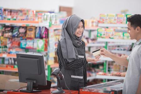 Einkaufen in bargeldlosen Zahlungen. glücklicher Kunde, der Lebensmittel im Supermarkt oder im Supermarkt kauft mit Kreditkarte bezahlt