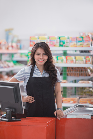 portrait of young attractive shopkeeper at cash register in a store Stock fotó
