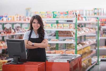 Porträt des lächelnden asiatischen weiblichen Kassiererpersonals, das am Bargeldschalter im Supermarkt steht Standard-Bild