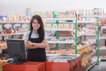 Portrait of smiling asian female cashier staff standing at cash counter in supermarket Stockfoto