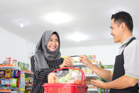 female customer paying her bills with credit card at the cashier in supermarket Stock Photo