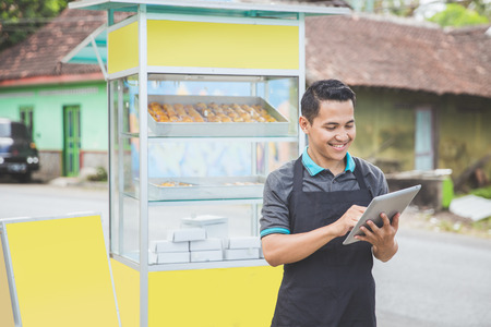asian man business owner using tablet pc while standing in front of his food stall. street food concept
