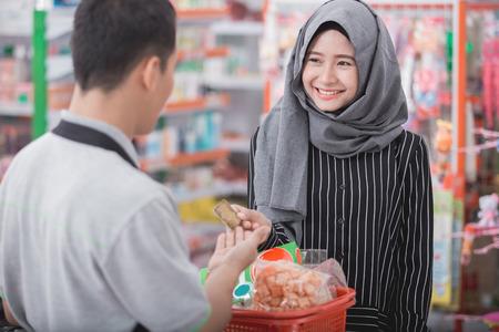식료품 점에서 신용 카드로 쇼핑을하는 행복 이슬람 여자의 초상화