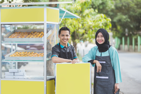 muslim woman and man small business owner standing proudly in front of their food stall. selling halal product Reklamní fotografie