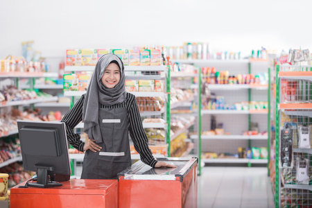 portrait of young attractive woman wearing head scarf at cash register in a store