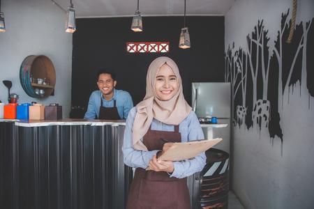 Happy asian male waiter using apron writing order. muslim entrepreneur concept 写真素材