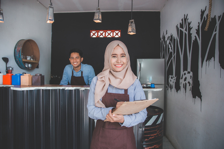Happy asian male waiter using apron writing order. muslim entrepreneur concept Stok Fotoğraf
