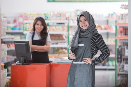 smiling muslim woman standing in front of the shop where she works