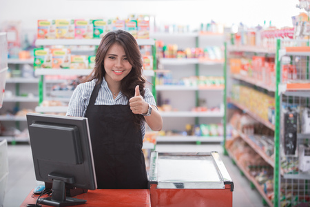 female cashier showing thumb up while standing in the cash register in supermarket Archivio Fotografico