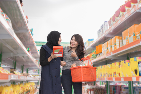 two woman friend buying some stuff at grocery store together Stock Photo