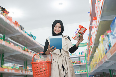 asian muslim woman buying some halal product at supermarket