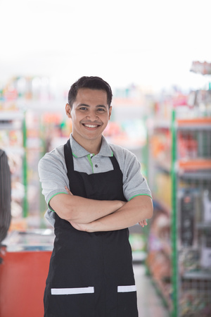 success supermarket owner standing in front of his shop