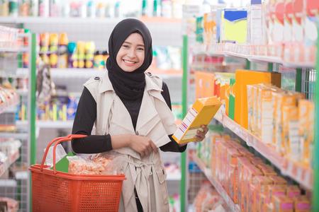 魅力的な女性のイスラム教徒の客がスーパー マーケットでいくつかの製品を購入します。