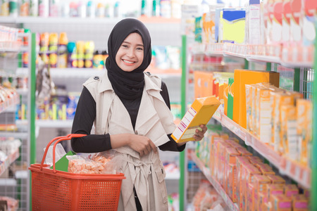attractive female muslim customer buy some product at supermarket