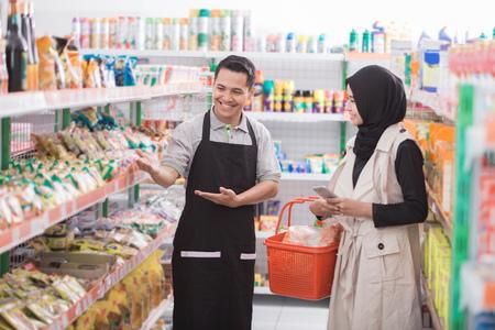 Retrato de comerciante masculino está ayudando a un cliente femenino musulmán en un supermercado