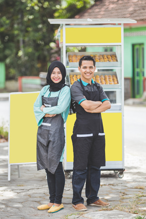 イスラム教徒の女性と男性の小さなビジネスのオーナーは、彼らの屋台の前で誇らしげに立っています。ハラル製品の販売