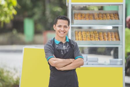właściciel małej firmy stojącej dumnie przed swoim stoiskiem z jedzeniem