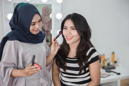 Beauty muslim make up artist applying cosmetic. Girl gets blush on the cheekbones Stock Photo