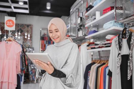 Ritratto di una giovane imprenditrice musulmana con un bel sorriso in possesso di tavoletta digitale mentre in piedi nella sua boutique di moda, proprietario femminile