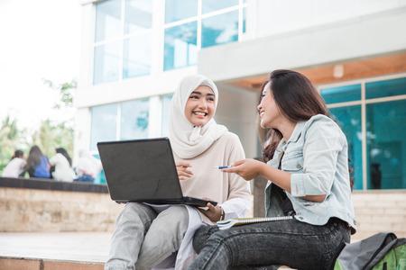 Porträt von zwei attraktiven asiatischen College-Student , der Laptop auf dem Campus verwendet Standard-Bild - 92565324