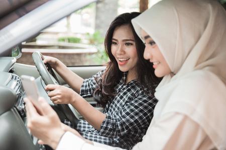 차를 운전하는 동안 친구에 게 그녀의 휴대 전화를 게재하는 젊은 여자의 초상화. GPS를 통한 방향 제시 스톡 콘텐츠