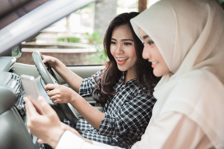 portrait of young woman showing her mobile phone to friend while driving a car. Giving direction via GPS