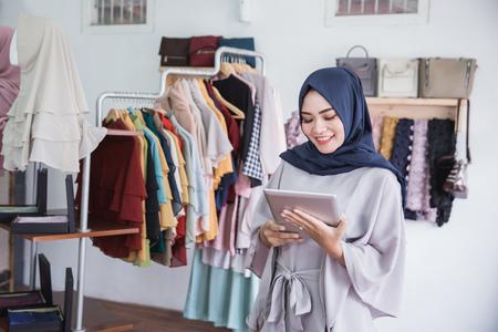 Neugeschäft starten. Schöne junge moslemische asiatische Frau, welche die digitale lächelnde Tablette bei der Stellung am Bekleidungsgeschäft verwendet