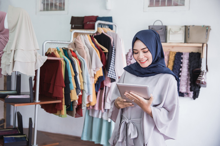 Starting new business. Beautiful young muslim asian woman using digital tablet smiling while standing at the clothing store 스톡 콘텐츠