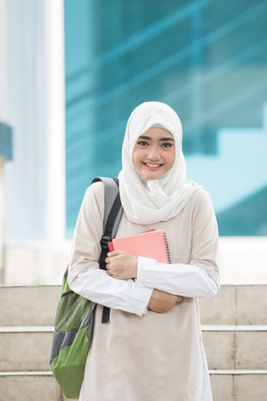 cheerful asian female university students wearing head scarf walking on campus Stock Photo