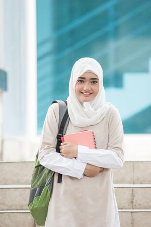 cheerful asian female university students wearing head scarf walking on campus Standard-Bild