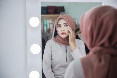 거울에 그녀의 얼굴을보고 hijab와 불행 이슬람 여자 스톡 콘텐츠 - 92566388