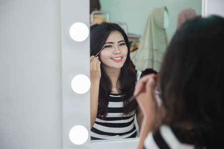 beautiful asian woman applying cosmetic with a brush on her eyelids Stock Photo