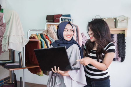 muslim asian woman entrepreneur team using laptop in her small fashion store 스톡 콘텐츠