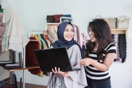 moslim Aziatische vrouw ondernemer team met behulp van laptop in haar kleine mode winkel
