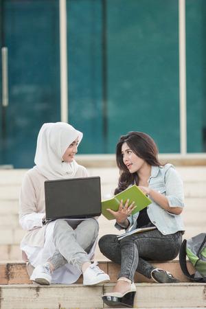 キャンパスでラップトップを使用して2人の魅力的なアジアの大学生の肖像画