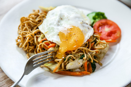 close up portrait of homemade indonesian fried noodle with fried egg for breakfast Banco de Imagens