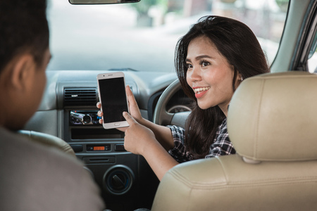 Retrato del taxista mujer joven que busca la dirección vía GPS en su teléfono móvil Foto de archivo - 92565569