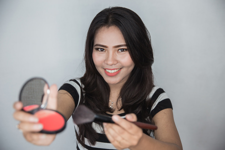 happy young asian woman showing her make up powder to camera. makeup tutorial concept. focus on woman face