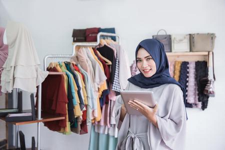 Starten Sie neue Unternehmen . Schöne junge muslimische asiatische Frau , die digitale Tablette beim Stehen am Bekleidungsgeschäft betrachtet