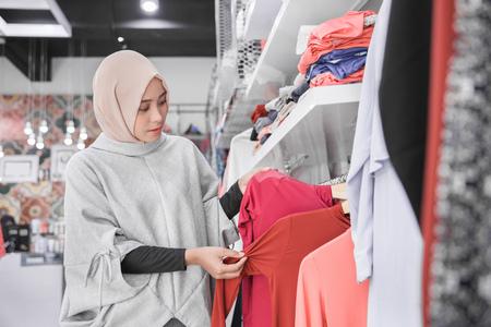 Mooie opgewonden moslim vrouw met hoofddoek kijken blouse in mode winkel Stockfoto