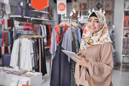 Portret van een jonge moslimonderneemster die met mooie glimlach digitale tablet houden terwijl status in haar manierboutique, vrouwelijke eigenaar