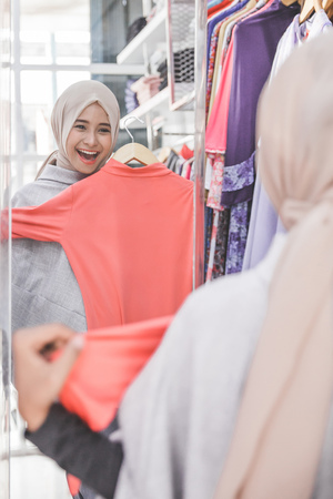excited asian muslim woman trying new clothes at fashion store