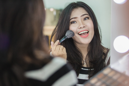 Beauty woman applying makeup. Beautiful girl looking in the mirror and applying cosmetic. Girl gets blush on the cheekbones Stock Photo