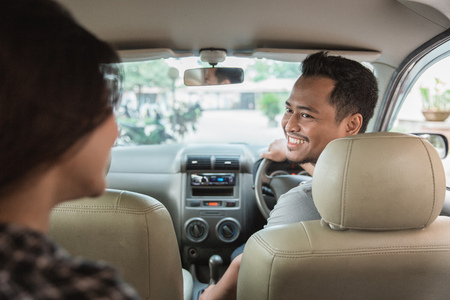 彼の顧客を歓迎するアジアの男性タクシー運転手