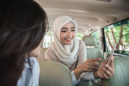 portrait of asian woman showing direction to the driver using GPS in her mobile phone Stock Photo